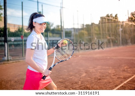 Attractive brunette playing tennis and smiling at camera. Healthy modern lifestyle with sportswoman and accessories - stock photo