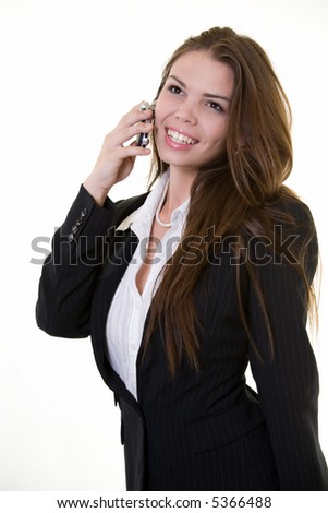 Attractive brunette smiling business woman holding and talking on cell phone wearing a dark colored business jacket - stock photo