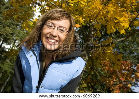 Attractive brunette smiling in the park on the fall - stock photo