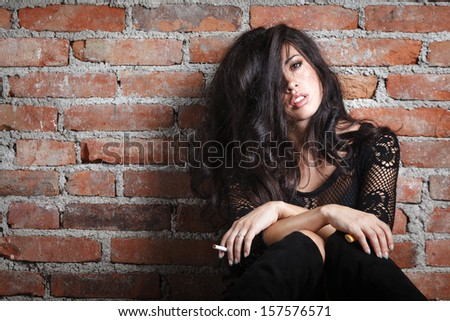 Attractive brunette smoking on wall background - stock photo