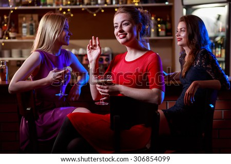 Attractive brunette with two pretty friends in cocktail bar - stock photo