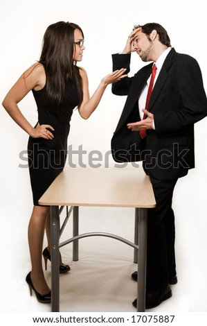 Attractive brunette woman and business man having an intense discussion each standing on opposite sides of a desk