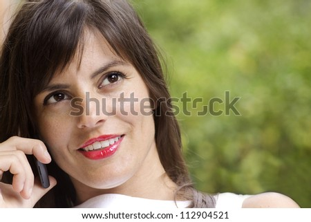 attractive brunette woman at phone against natural background