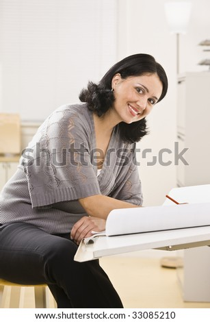 Attractive brunette woman drawing on white paper on board, smiling at camera. Vertical - stock photo