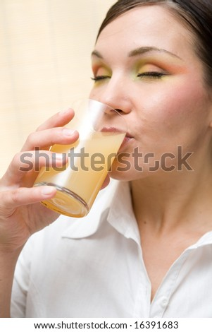 attractive brunette woman drinking orange juice