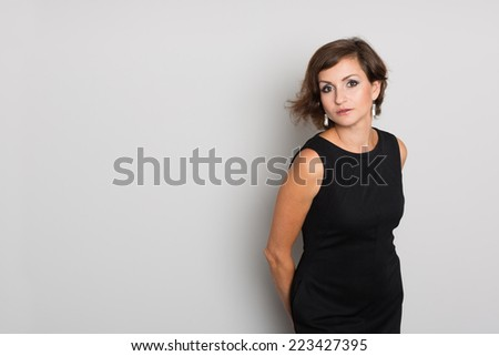 Attractive brunette woman in a black dress on a background of a gray wall. Woman 36 years old. - stock photo