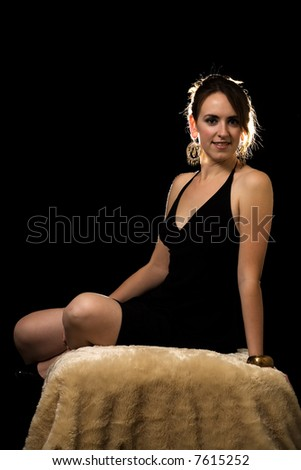 Attractive brunette woman in black dress  sitting on a fur covered stool over black