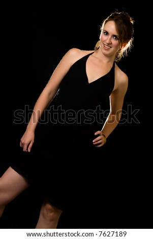 Attractive brunette woman in black dress  standing over black - stock photo
