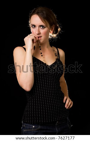 Attractive brunette woman in black playing with a necklace standing on black