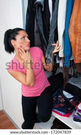 attractive brunette woman in front of closet full of clothes choosing what to wear - stock photo