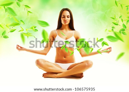 attractive brunette woman in yoga pose and leaves - stock photo