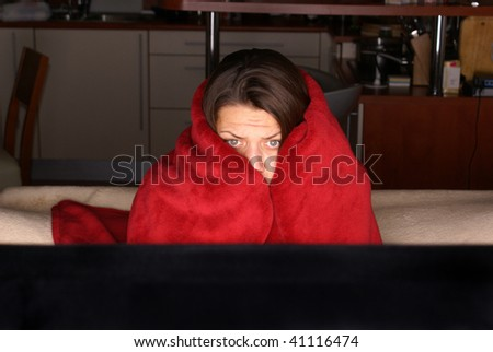 attractive brunette woman on sofa watching tv - stock photo