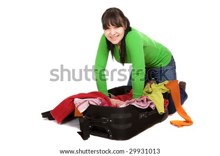 attractive brunette woman packs her clothes. - stock photo
