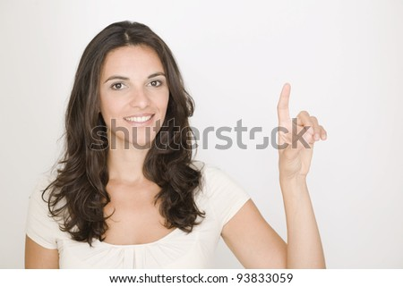 Attractive brunette woman pointing on a virtual screen - stock photo