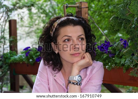 Attractive brunette woman sitting at an outdoor table on a leafy green patio watching something off to the right of the screen - stock photo