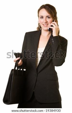 Attractive brunette woman wearing black business suit holding briefcase while talking on a cell phone