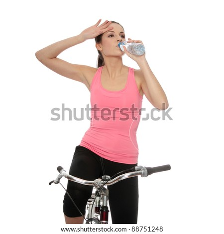 Attractive brunette woman with bike drinking water. over white background - stock photo