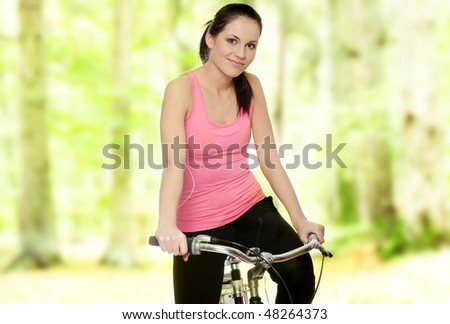 Attractive brunette woman with bike in forest - stock photo