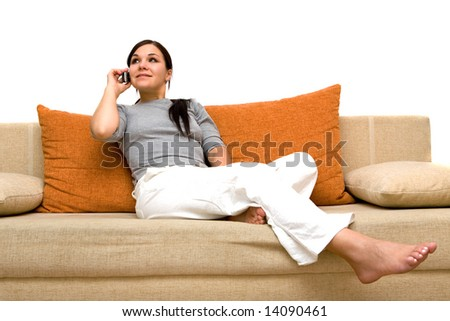 attractive brunette woman with cell phone on sofa