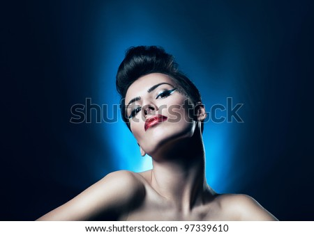attractive brunette woman with red lips in blue light - stock photo