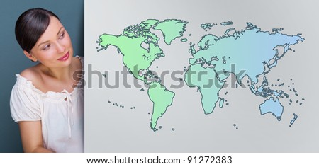 Attractive brunette young woman standing near board with world map. International service or traveling concept - stock photo