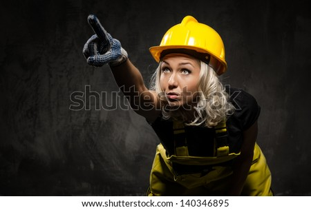 Attractive builder woman showing something with the hand, studio shot