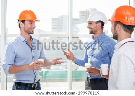 Attractive builders are drinking coffee on a break. They are talking and smiling. The men are looking at each other with trust  - stock photo