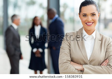 attractive business executive with arms folded in office - stock photo
