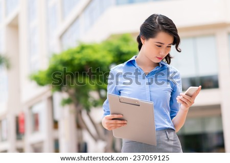 Attractive business lady reading message on her phone - stock photo