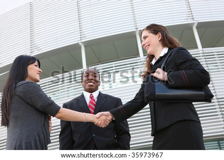 Attractive business man and women team at office building shaking hands