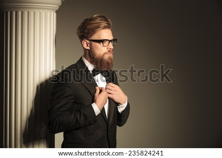 Attractive business man fixing his suit with both hands while looking away from the camera. - stock photo