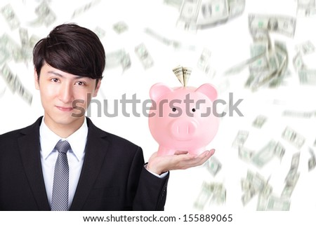 Attractive business man holding pink piggy bank with money falling background, asian model - stock photo