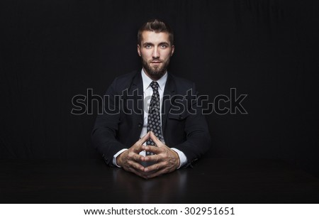 Attractive business man in front of a black background - stock photo