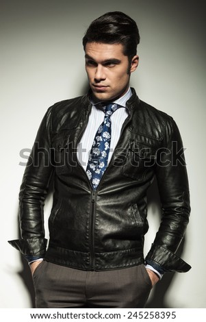 Attractive business man in leather jacket, looking away from the camera with his hands in pockets. - stock photo