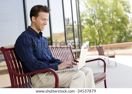 Attractive business man on his laptop outside an office building - stock photo