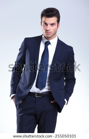 Attractive business man posing on grey studio background with his hands in pockets, looking at the camera. - stock photo