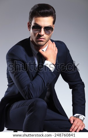Attractive business man sitting while holding one hand to his neck and the other one on his leg. - stock photo