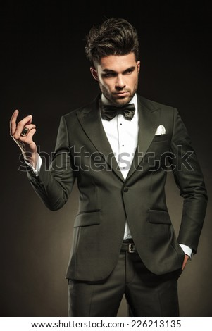 Attractive business man snapping his fingers while holding one hand in pocket, looking away from the camera. On black studio background. - stock photo