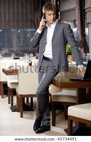 Attractive business man speaks by a mobile phone at restaurant - stock photo