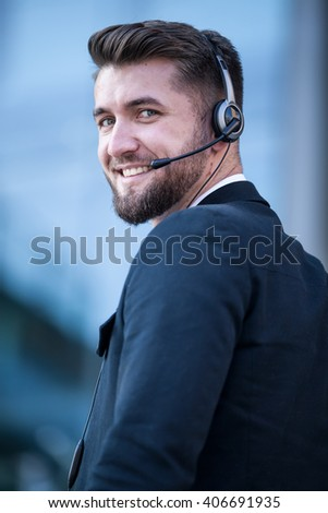 Attractive business man with a headset is looking over his shoulder