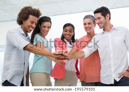 Attractive business people joining hands in the workplace to unite as one - stock photo