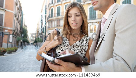 Attractive business people meeting outdoors and looking at paperwork - stock photo