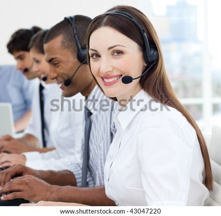 Attractive business people with headset on working in a call center - stock photo