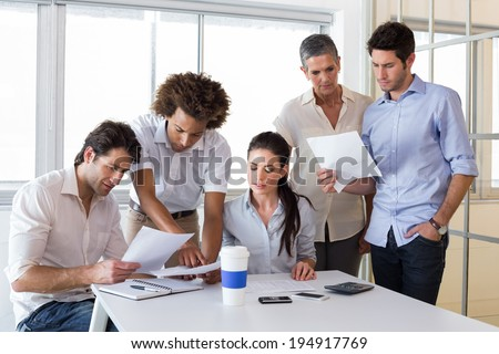 Attractive business people working hard and discussing in the office - stock photo