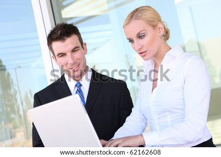 Attractive business team on laptop at office (Focus on Man) - stock photo