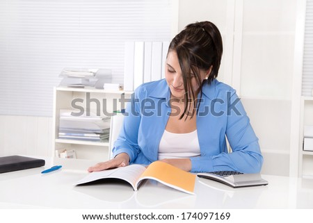 Attractive business woman at desk. - stock photo