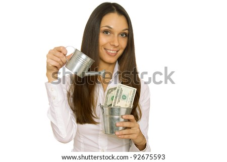 Attractive business woman holding money in a bucket and pours ikhi from a watering can. Isolated on white background - stock photo