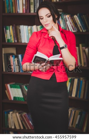 attractive business woman in office attire standing against the  - stock photo