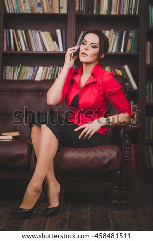attractive business woman in office clothes sitting on a leather couch korchnevom and talking on the phone, behind her are large bookshelves. communication concept - stock photo