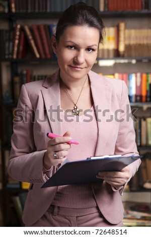 Attractive business woman in pink suit holding clipboard and pink  highlighter in library - stock photo